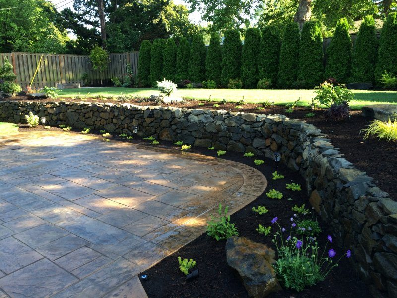 stamped concrete-patio-rock wall-plants-backyard landscape
