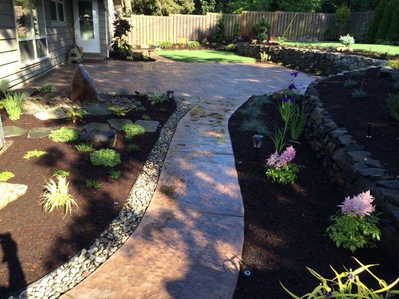 stamped concrete-walkway-water feature-bubbler-plants-rock wall-drain